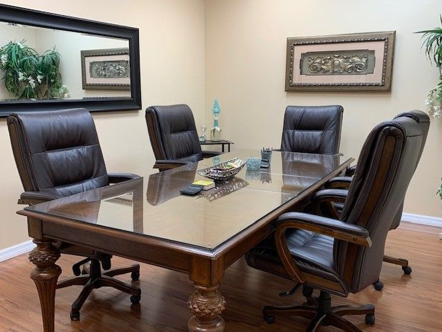 Conference room with large table and five leather chairs