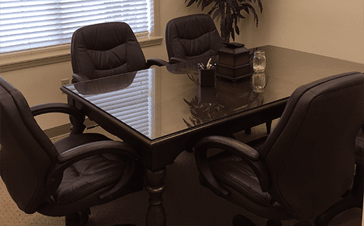 Conference room with table and four leather chairs